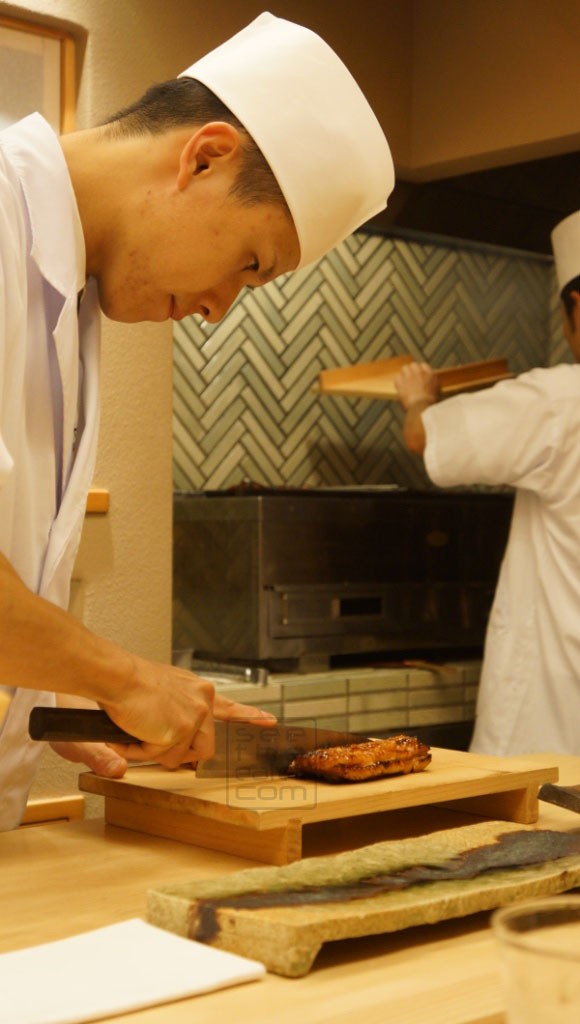 Chef chopping the fresh grilled unagi (eel)